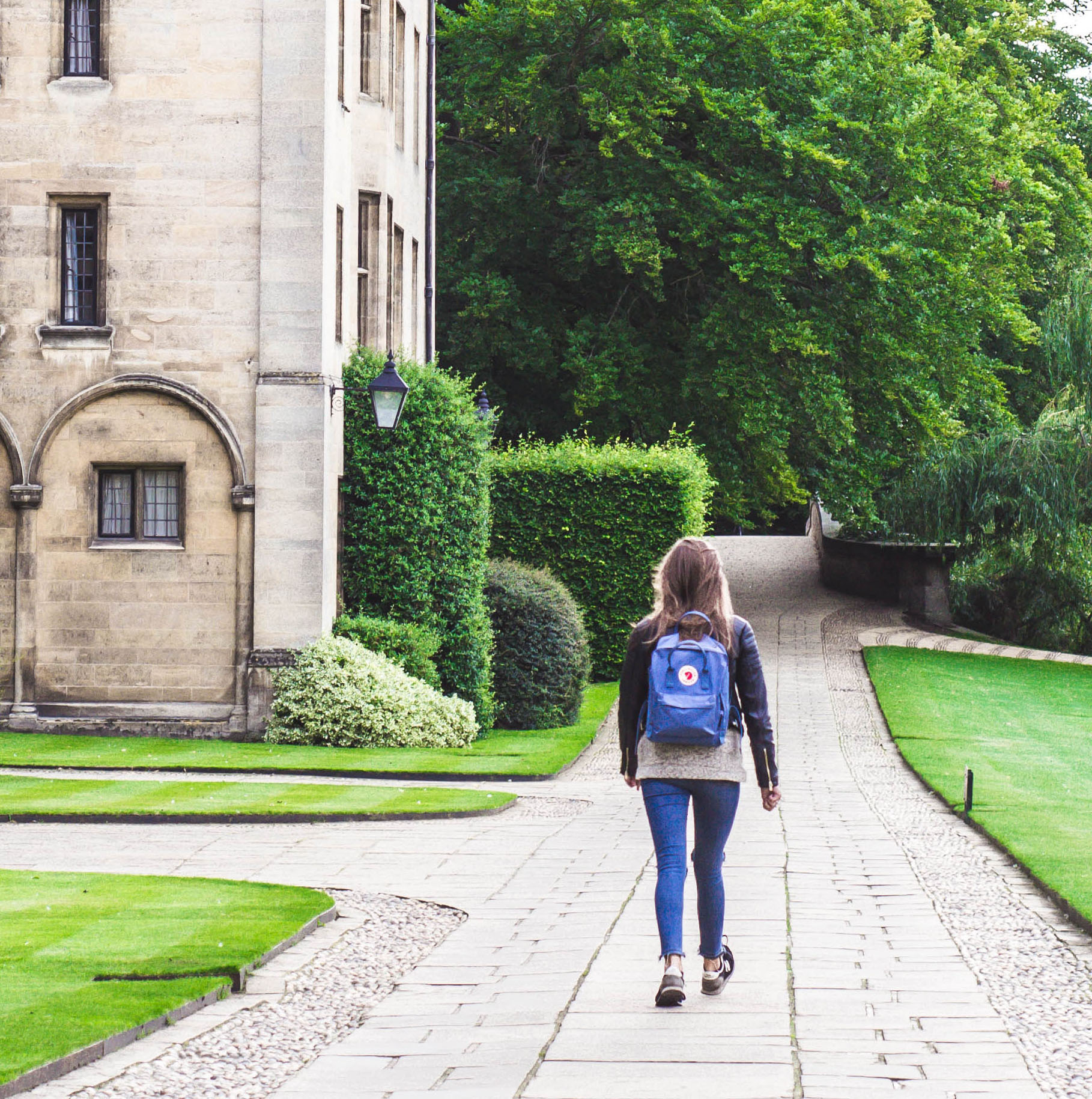 A student walking on a college campus wearing a backpack