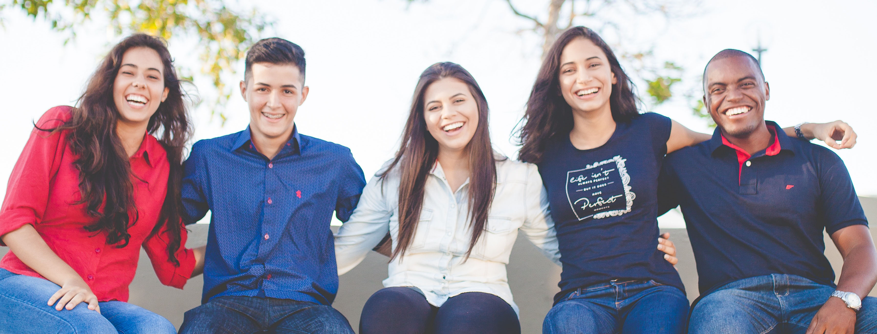 Five students sitting with their arms around each other smiling at the camera